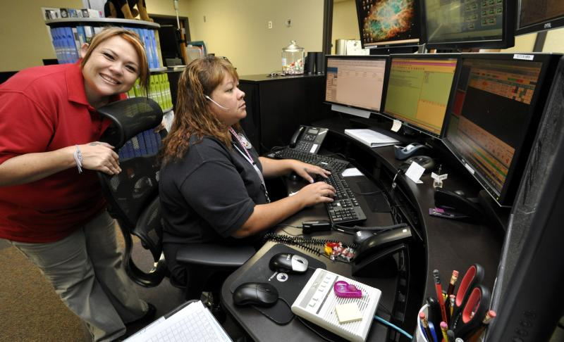 Woman Smiling at Camera While Another Woman Works at Workstation