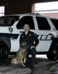Police Officer Posing with Dog by Police Car